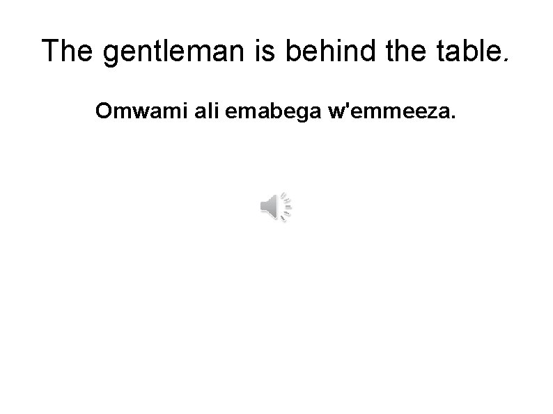 The gentleman is behind the table. Omwami ali emabega w'emmeeza.