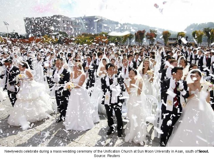 Newlyweds celebrate during a mass wedding ceremony of the Unification Church at Sun Moon