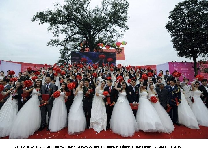 Couples pose for a group photograph during a mass wedding ceremony in Shifang, Sichuan