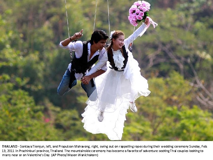 THAILAND - Sontaya Tiemjun, left, and Praputson Mahavong, right, swing out on rappelling ropes