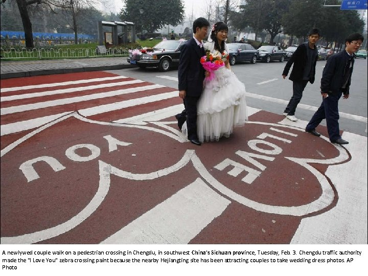 A newlywed couple walk on a pedestrian crossing in Chengdu, in southwest China's Sichuan