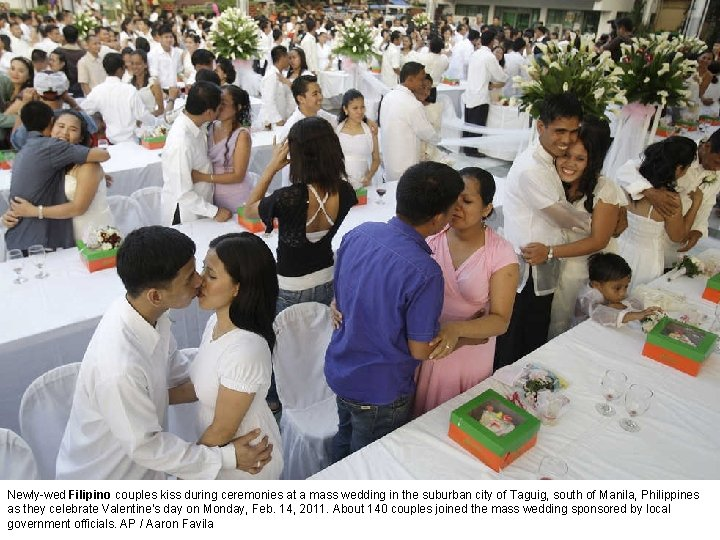 Newly-wed Filipino couples kiss during ceremonies at a mass wedding in the suburban city