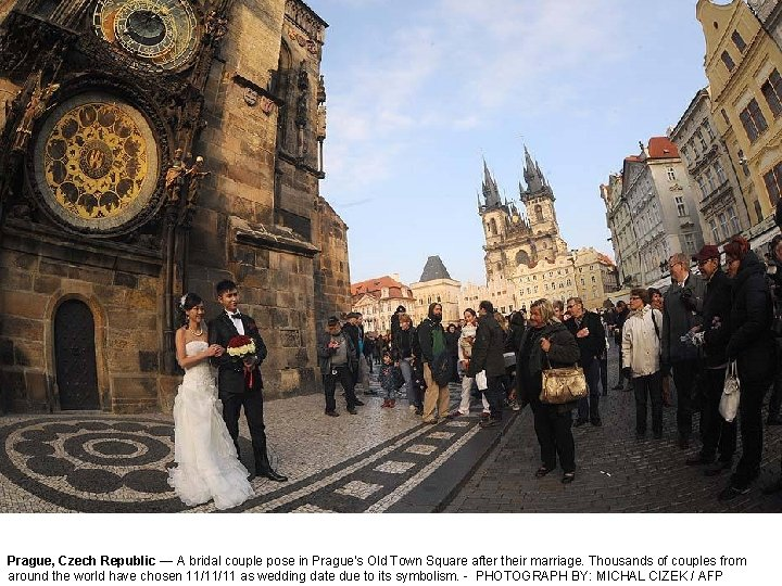 Prague, Czech Republic — A bridal couple pose in Prague's Old Town Square after