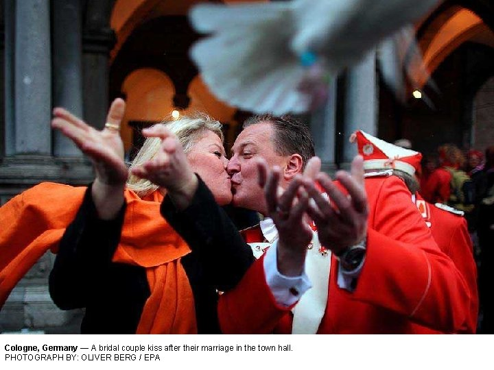 Cologne, Germany — A bridal couple kiss after their marriage in the town hall.