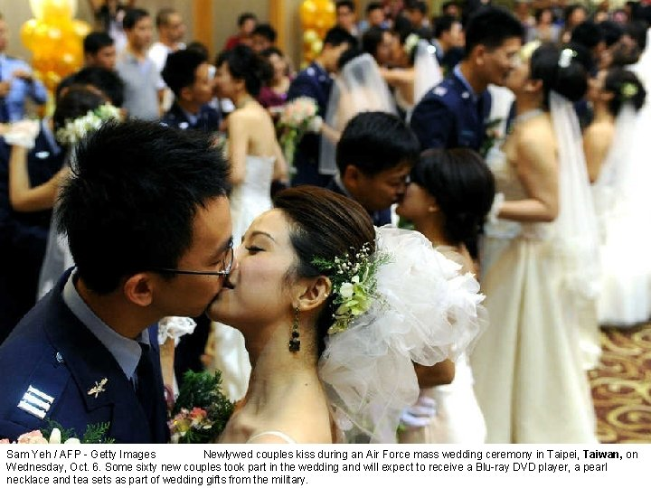 Sam Yeh / AFP - Getty Images Newlywed couples kiss during an Air Force