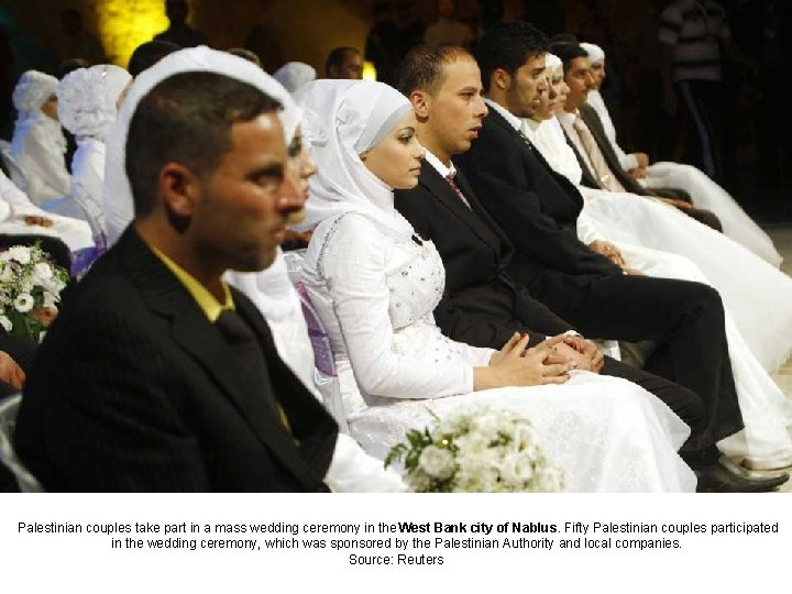 Palestinian couples take part in a mass wedding ceremony in the West Bank city